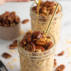 Pouring maple syrup into a jar of healthy maple pecan overnight oats.