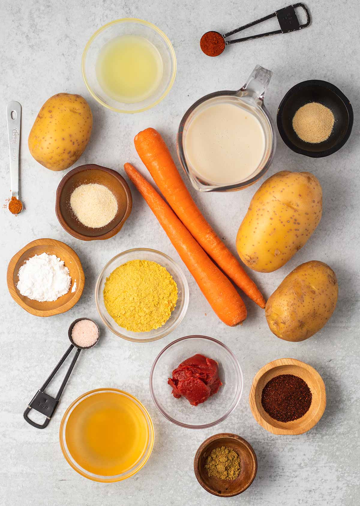 Ingredients for vega nacho cheese sauce, some are in small bowls and measuring spoons: potatoes, carrots, garlic powder, onion powder, lime juice, cayenne pepper, chili powder, cornstarch, nutritional yeast, salt, tomato paste, and cumin.