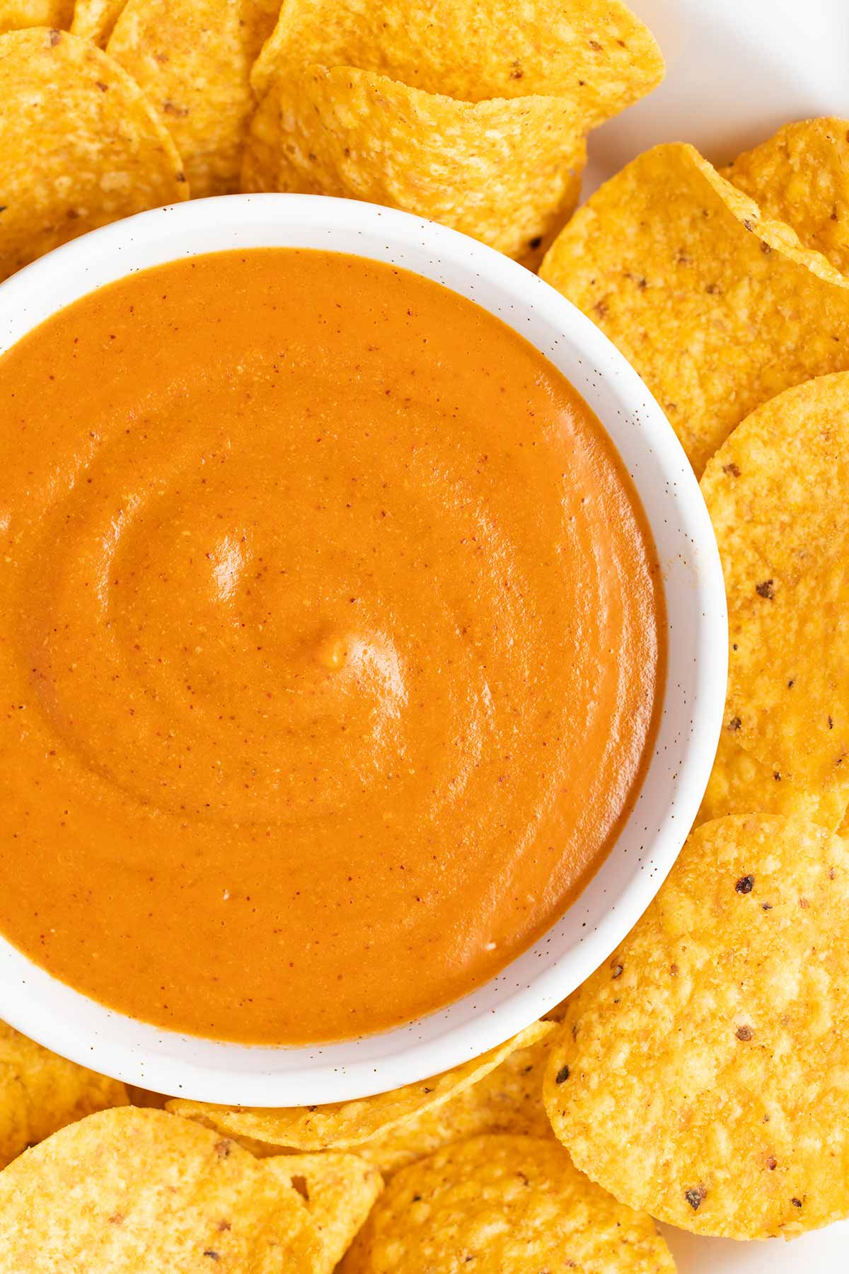 A bowl of vegan nacho cheese surrounded by round tortilla chips.