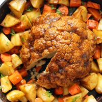 Whole roasted cauliflower in a large cast iron pan surrounded by carrots and potatoes.