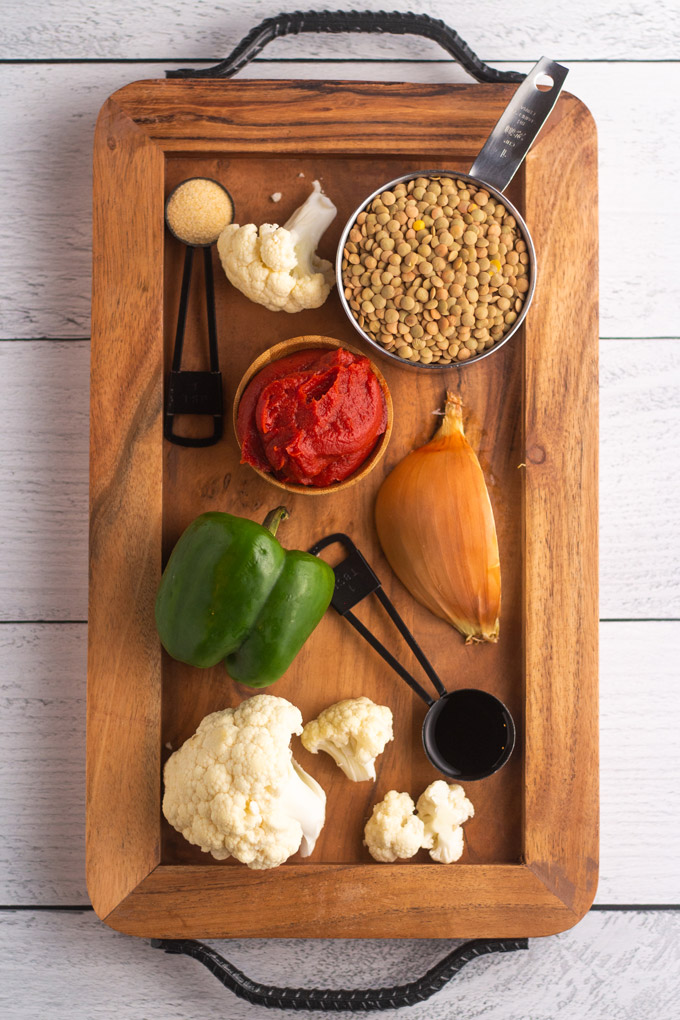 Vegan sloppy joe mix ingredients on a wooden board - a cup with lentils, a small bowl with tomato paste, a green bell pepper, some cauliflower florets, quarter of an onion and black measuring spoons containing garlic powder and Worcestershire sauce.