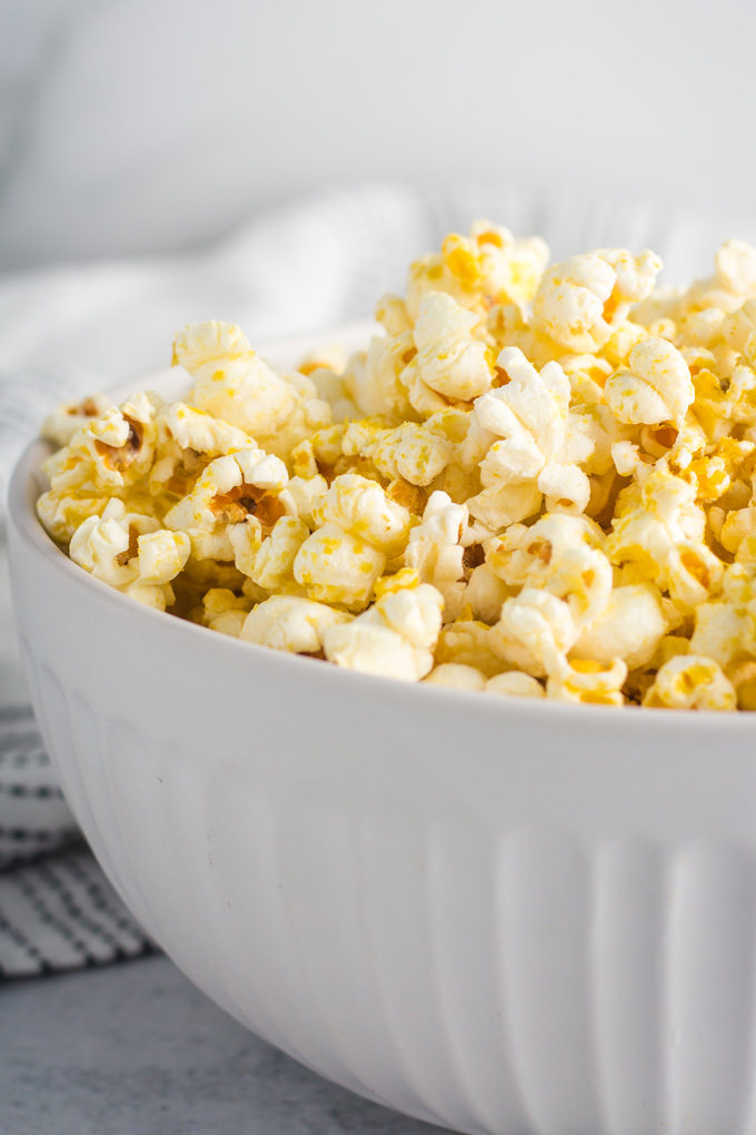 Homemade vegan popcorn in a white bowl seasoned with butter and nutritional yeast