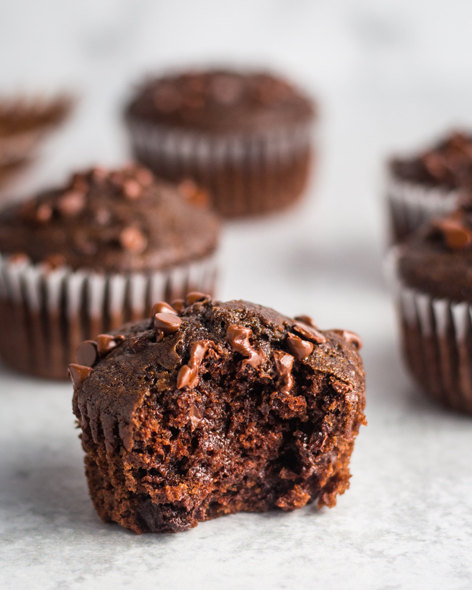 A few vegan chocolate muffins on a cement-style surface. The muffin in front has a bite taken out.