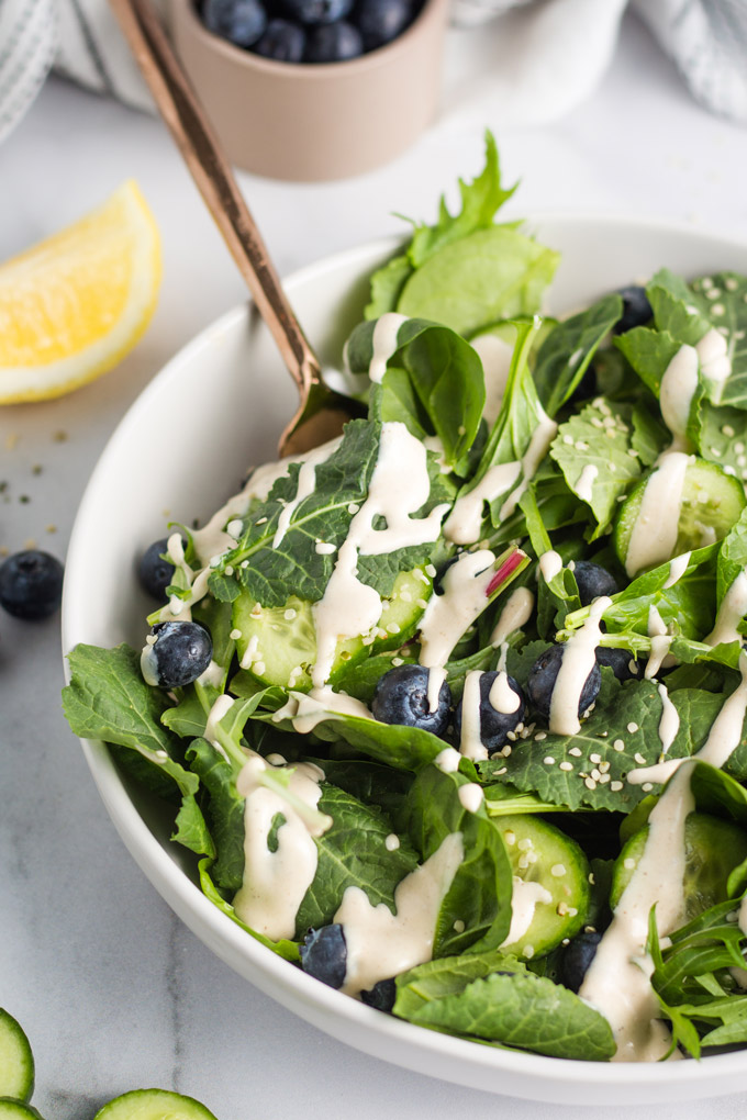 Blueberry Hemp Seed Salad in a large white bowl drizzled with a creamy tahini dressing with cucumbers.