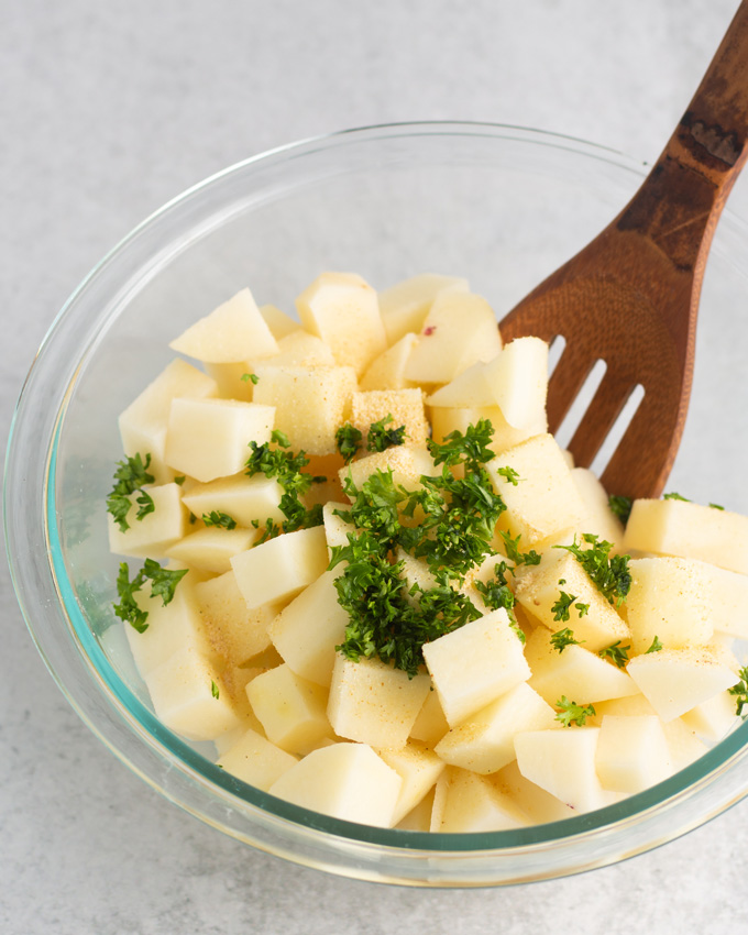 Peeled and cubed raw potatoes in a bowl with garlic powder and parsley.