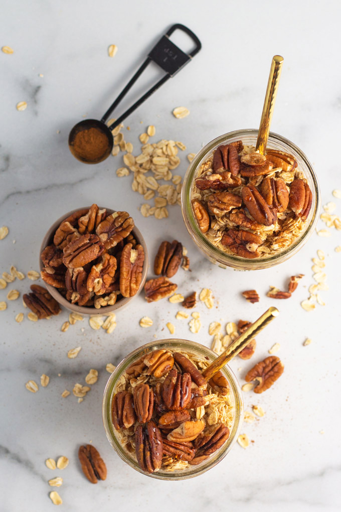 Overhead shot of two jars of maple pecan overnight oats next to a small bowl of pecans.