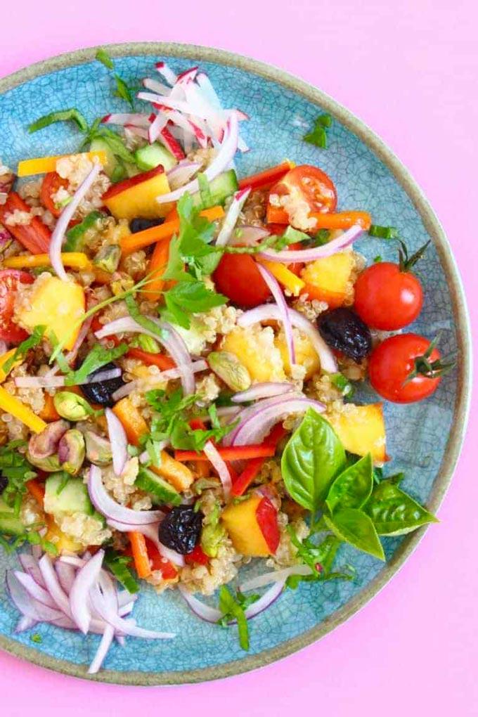 A blue plate with a nectarine quinoa buckwheat salad.