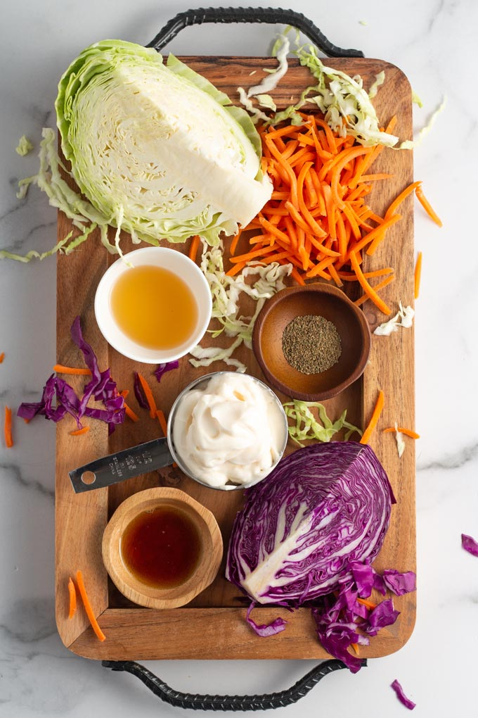 Ingredients for vegan coleslaw laid out on a wooden board: cabbage wedges, vegan mayo, shredded carrots, apple cider vinegar, maple syrup, and celery seed.