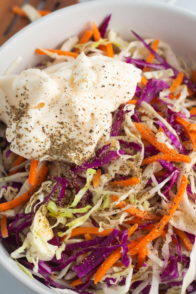Easy vegan coleslaw in a white bowl with red cabbage, green cabbage, carrots and vegan mayo.