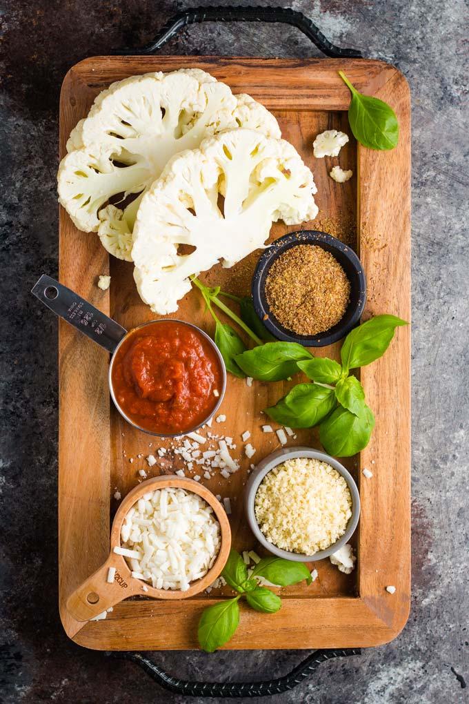 Ingredients for vegan cauliflower parm: cauliflower steaks, marinara sauce, flax egg, panko, and vegan mozzarella.