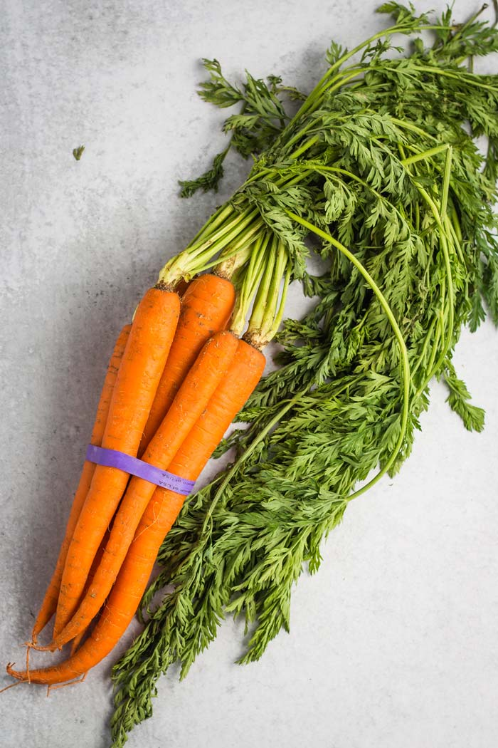 A bundle of carrots with the greens still attached.