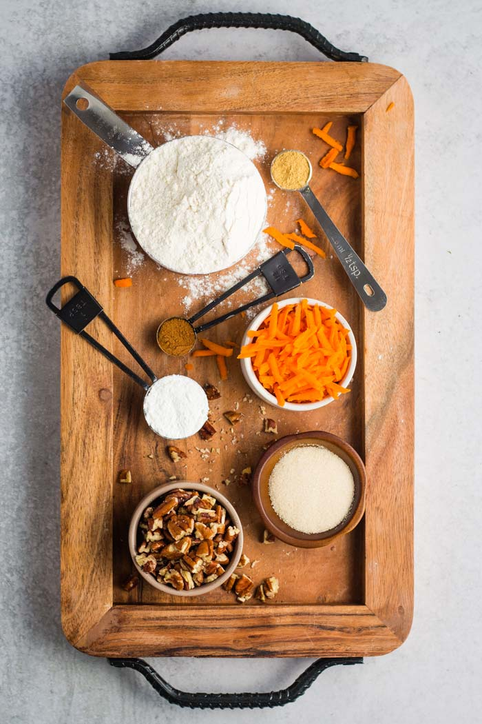 Ingredients for carrot cake pancakes laid out on a wooden board - flour, ginger, cinnamon, shredded carrots, baking powder, sugar, and pecans.
