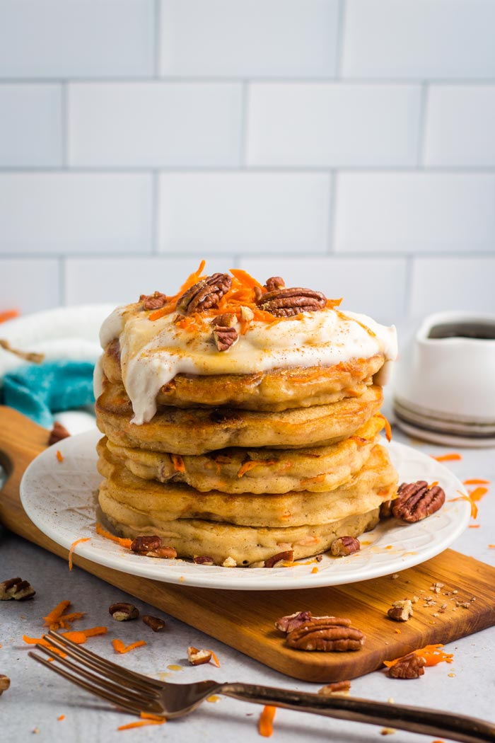 A stack of carrot cake pancakes topped with a coconut cream frosting.