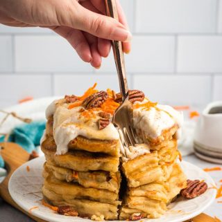 A fork taking a bite out of a stack of vegan carrot cake pancakes.