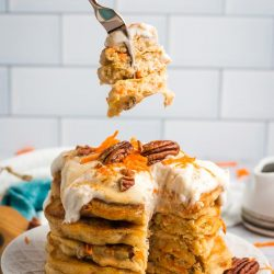 A fork posed over a stack of vegan carrot cake pancakes.