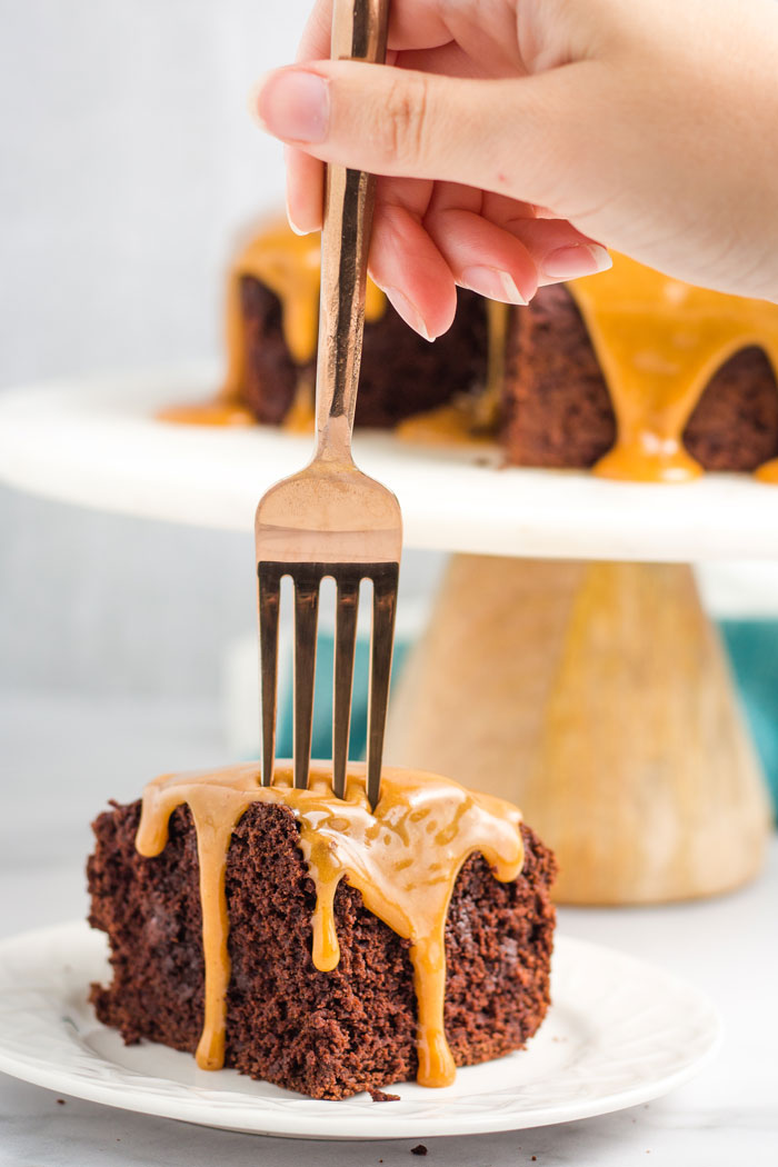 A fork piercing a slice of vegan peanut butter chocolate cake.