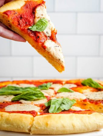 A piece of vegan pizza being held up above the whole pie.