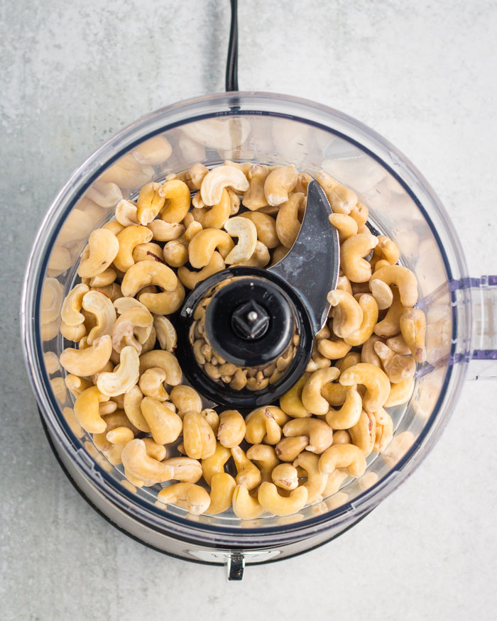 A food processor containing the ingredients for a vegan cheese: cashews, water, lemon juice, apple cider vinegar, and salt.