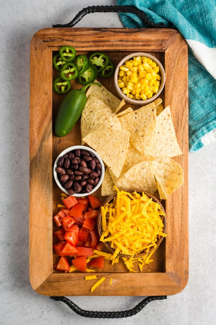 Some ingredients for vegan nachos on a wooden board: corn, jalapenos, beans, cheese, tomatoes, and tortilla chips.