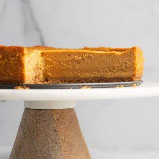 Vegan pumpkin cheesecake displayed on a cake stand