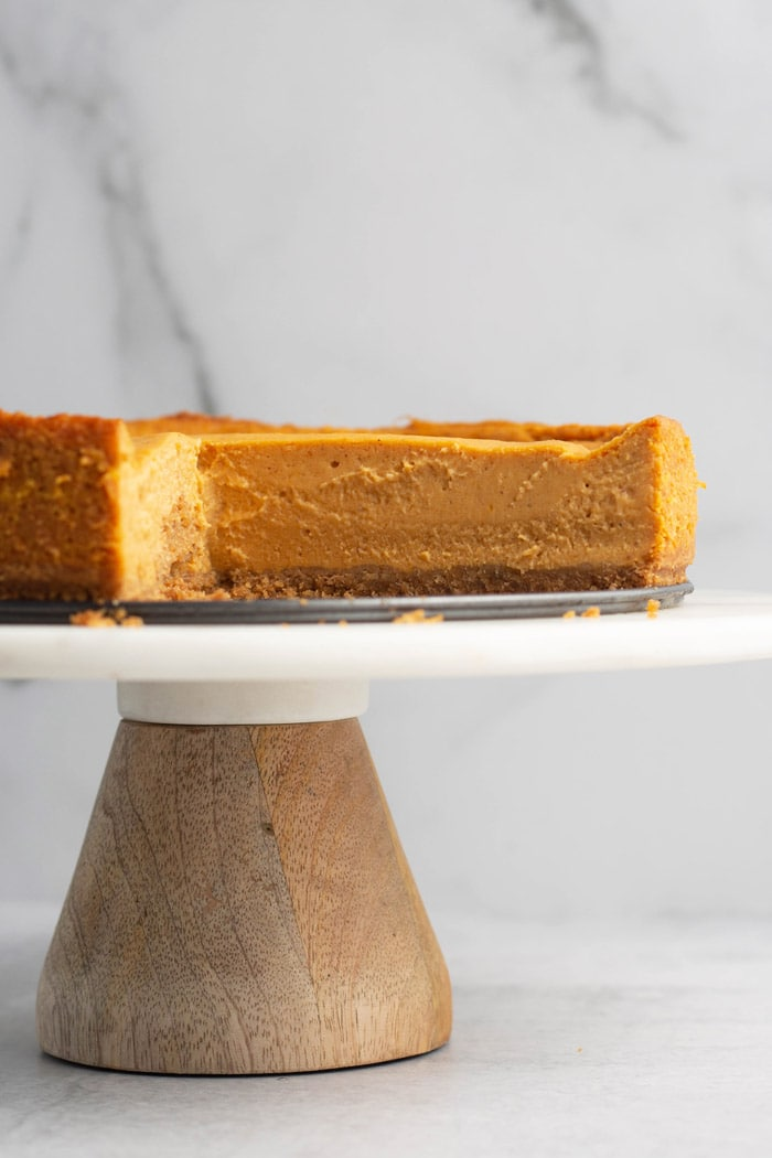 Vegan pumpkin cheesecake displayed on a cake stand