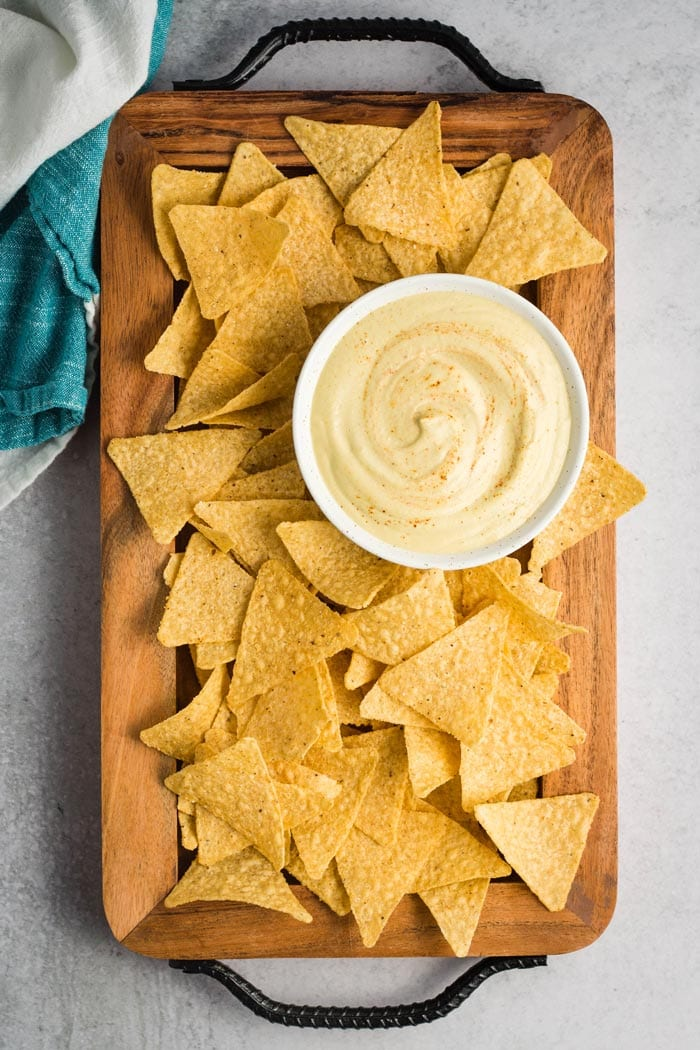 Creamy cashew vegan queso in a bowl surrounded by tortilla chips.