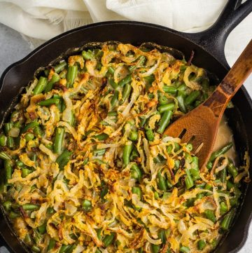 Vegan green bean casserole in a cast iron pan with a dark wooden spoon.