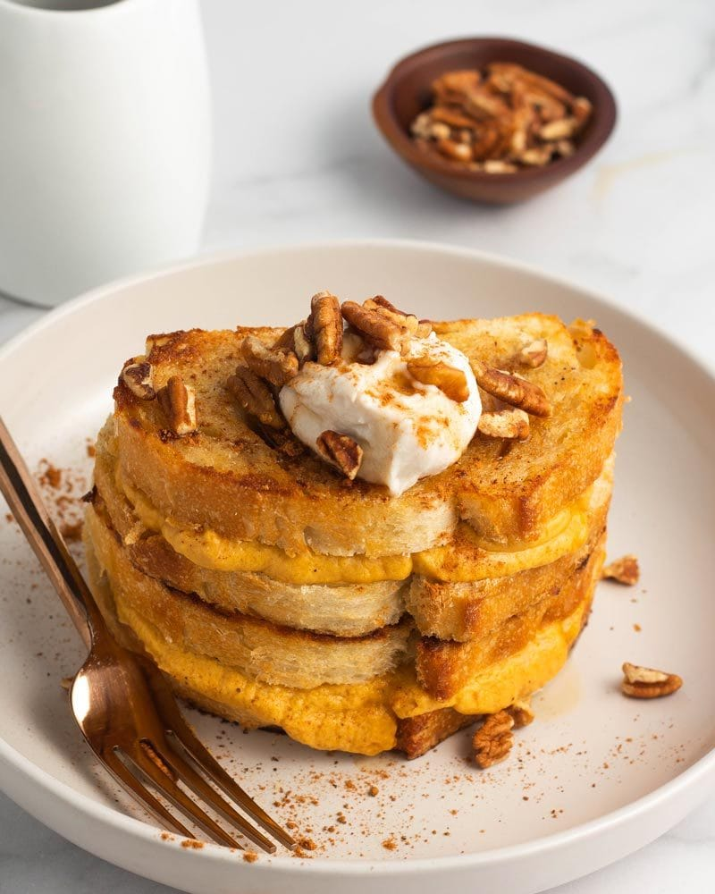 A stack of pumpkin stuffed french toast topped with vegan whipped cream.
