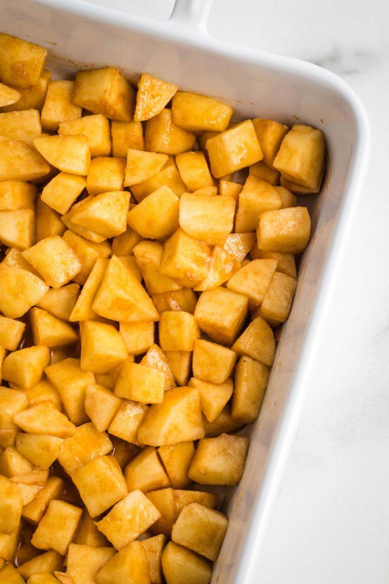 Apple crisp filling a white baking dish.
