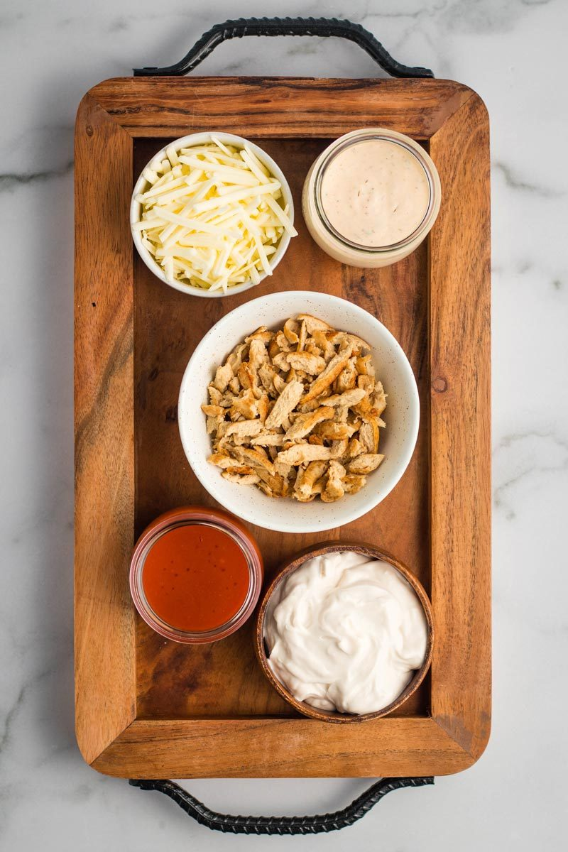 Ingredients for vegan buffalo dip on a wooden board: ranch, shredded cheese, vegan chicken, hot sauce, and cream cheese.