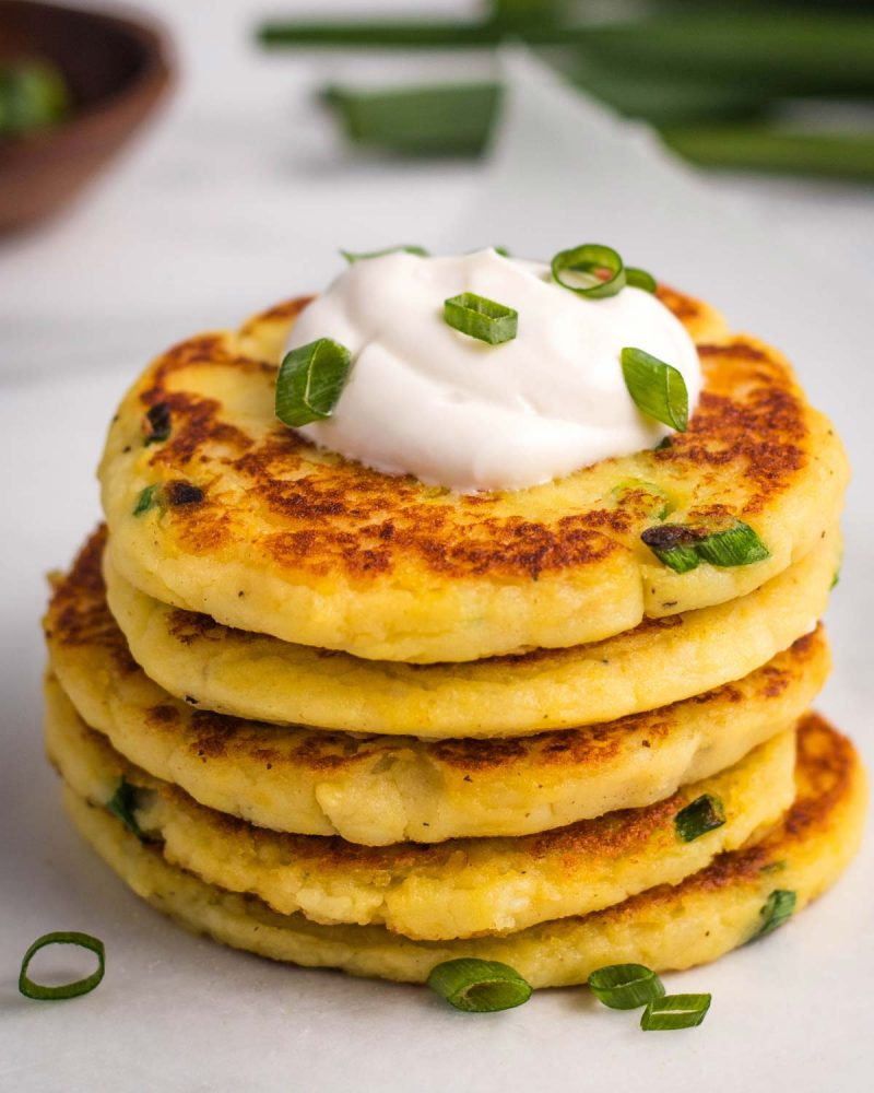 Mashed pancakes stacked in a pile topped with vegan sour cream and green onions.